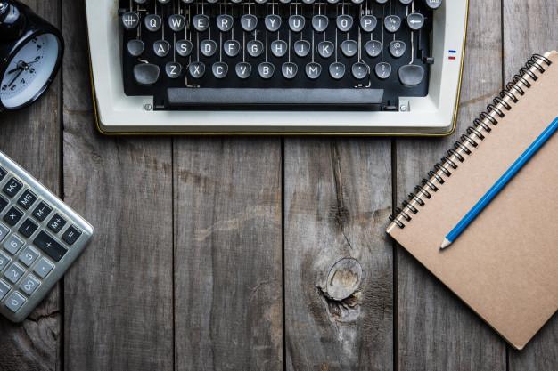 mao-retro-de-maquina-de-escrever-na-mesa-de-madeira_40800-161